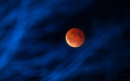 The moon glows a red hue during a total lunar eclipse Tuesday, April 15, 2014, as seen from the Milwaukee area. That eclipse was the first of four total lunar eclipses to take place between 2014 to 2015. (AP Photo/Milwaukee Journal-Sentinel, Mike De Sisti)